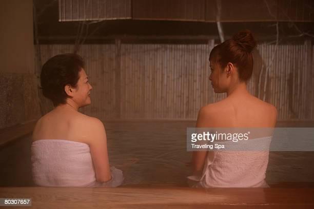 Two women soaking in hot tub, rear view