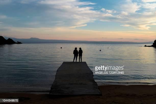 Two women speak on a jetty at the karagatsia beach on Ammouliani Island on October 2 2018