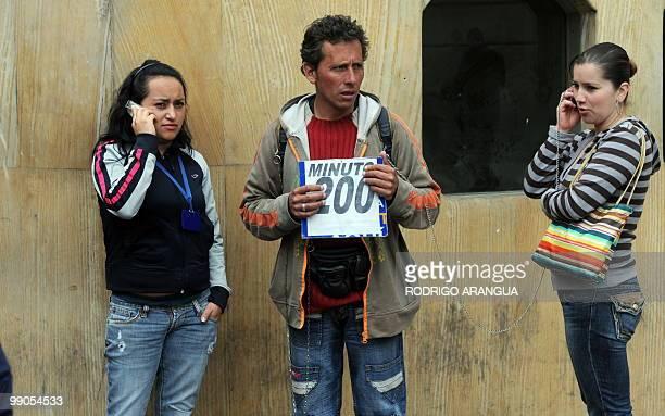 Two women speak on rented cell phones at a street in Bogota on may 12 2010 AFP PHOTO Rodrigo ARANGUA