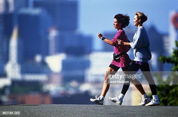 Two women speed walking in city, San Francisco, California, USA