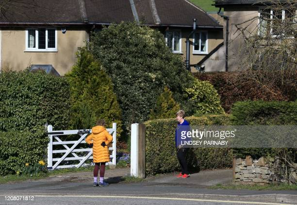 Two women stand a distance apart as they talk in Stoney Middleton village in Derbyshire central England on March 23 2020 Prime Minister Boris Johnson...
