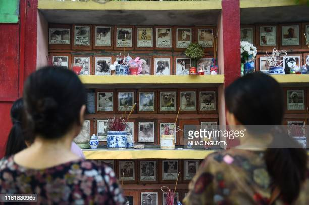 Two women stand before the plague of their pets after placing offerings at Te Dong Vat Nga pagoda which means all lives are equal a cemetary for pets...