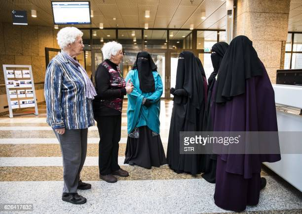 Two women stand next to women wearing niqab as they visit the Senate on November 23 2016 in the Hague the Netherlands Dutch MPs on November 29 2016...
