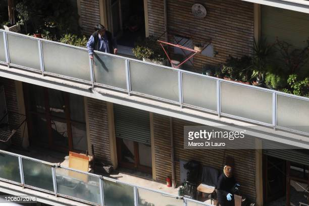 Two women stand on their balconies during lockdown on March 23 2020 in Rome Italy As Italy extends its nationwide lockdown to control the spread of...