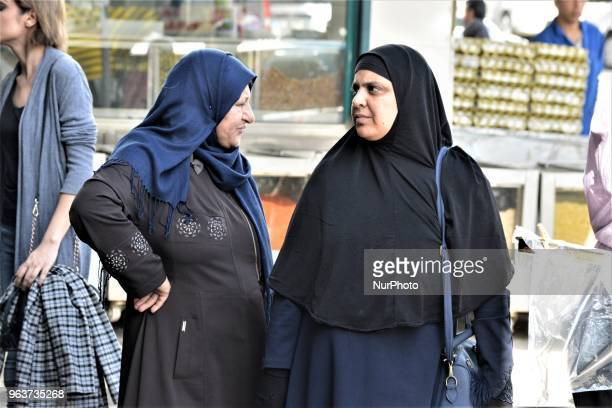 Two women stand outside a bazaar during the Muslim holy fasting month of Ramadan in the historic Ulus district of Ankara Turkey on May 27 2018