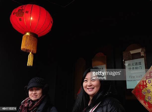 Two women stand under a lantern outside a Chinese restaurant as the Chinese community come together to welcome in the Chinese New Year on February 22...