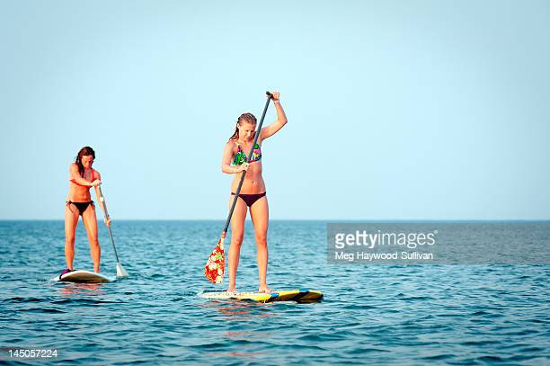 Two women stand up paddle board by the coast.