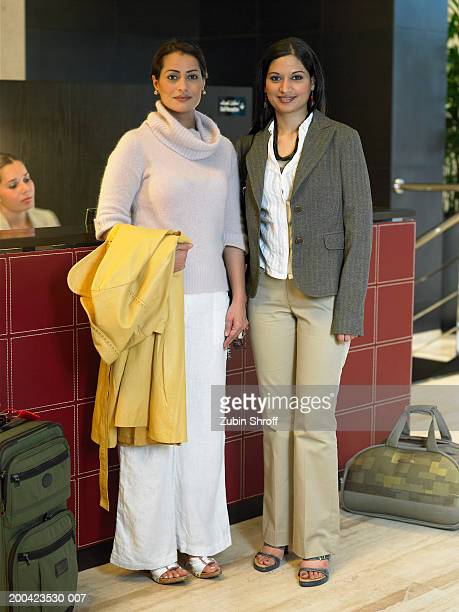 Two women standing at front desk of hotel lobby, portrait
