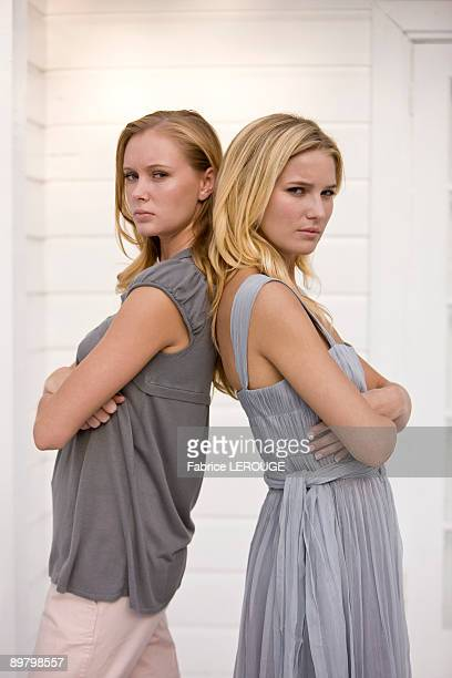 Two women standing back to back and looking serious