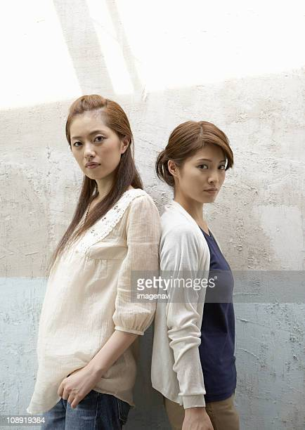 two women standing back to back - 背中合わせ ストックフォトと画像