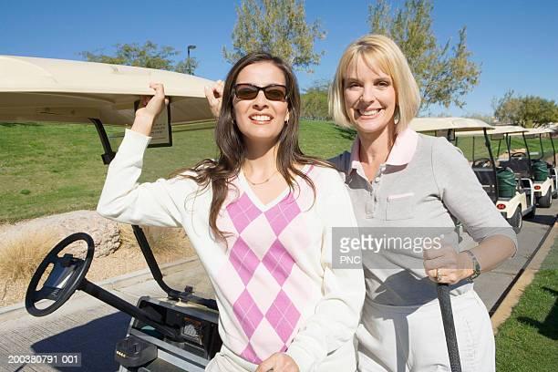 Two women standing beside golf cart, smiling, portrait