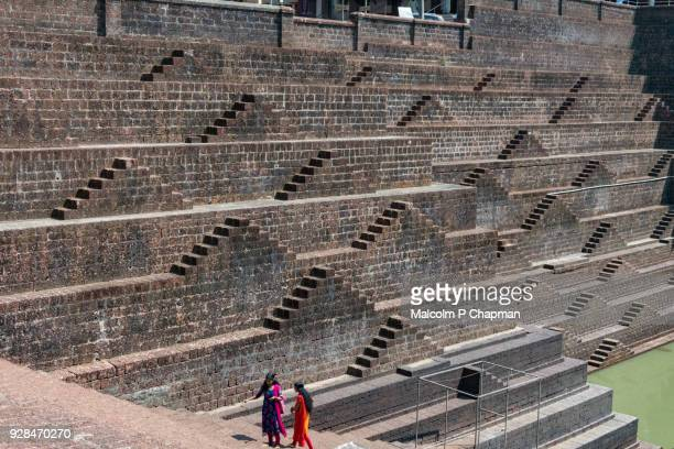 two women standing by stepwell and temple pond at sri subrahmanya (subramaniya) temple, peralassey, kannur, kerala - stepwell stock photos and pictures