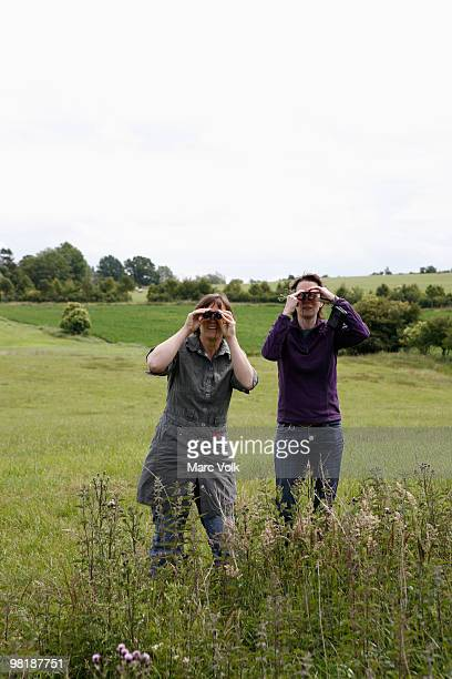 Two women standing in a field and using binoculars