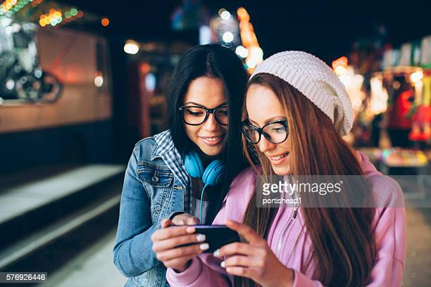 Two women standing in amusement park and using smart phone