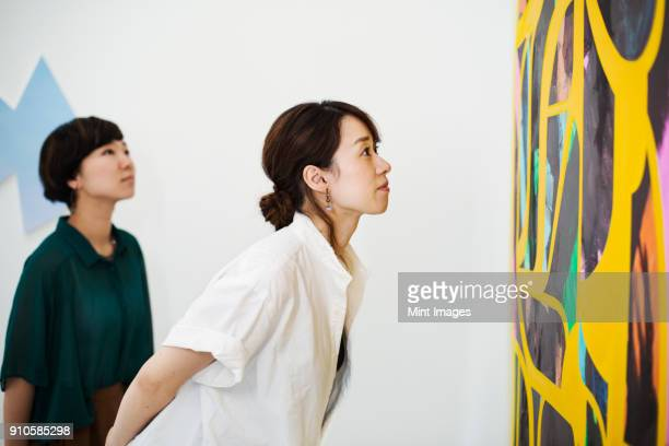 two women standing in an art gallery, looking at an abstract modern painting. - konstmuseum bildbanksfoton och bilder