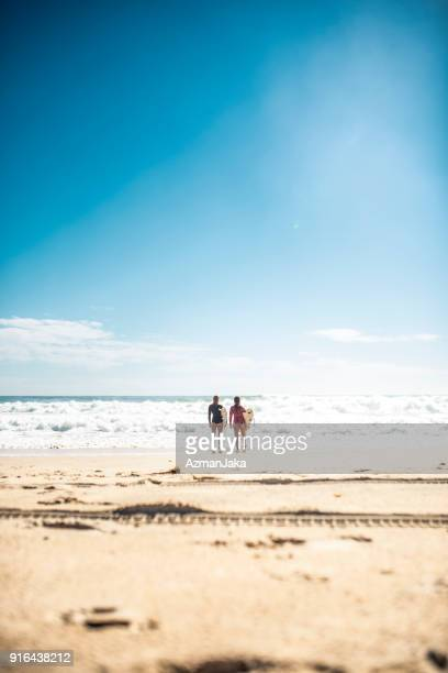 Two women standing in front of the ocean with surfboards