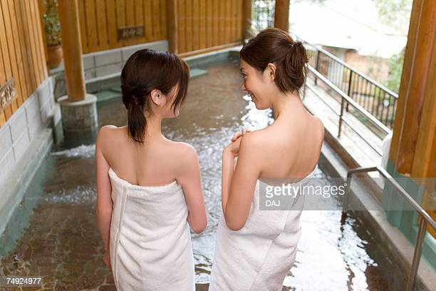 Two women standing in hot tub, hot spring, rear view, Japan