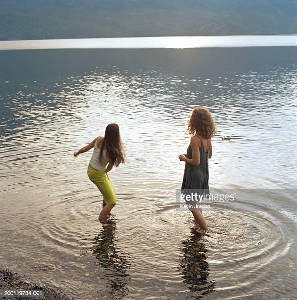 Two women standing in lake, skipping rock, rear view