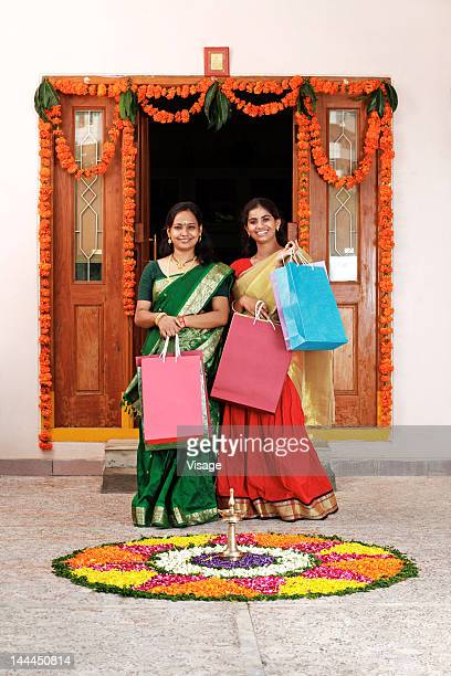 Two women standing near a pookalam