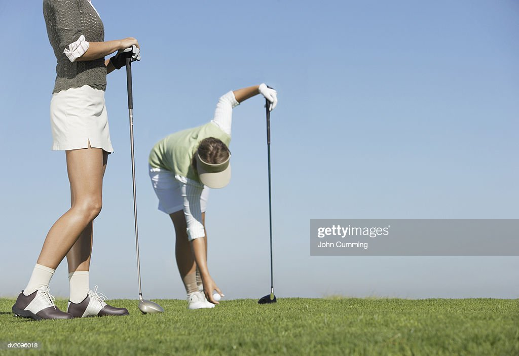 Two Women Standing on a Putting Green, One Picking Up a Golf Ball : Stock Photo