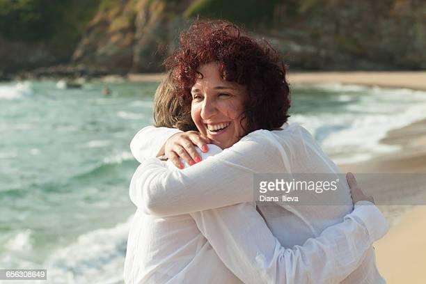 Two women standing on beach hugging