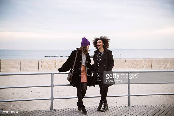 Two women standing on the boardwalk by the beach