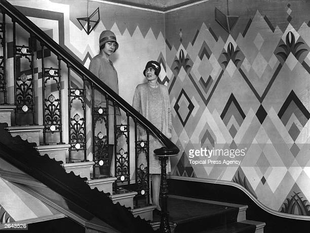 Two women standing on the stairs in the hall of Dorville House the premises of Rose and Blairman in Cavendish Square decorated in an 'art deco' scheme