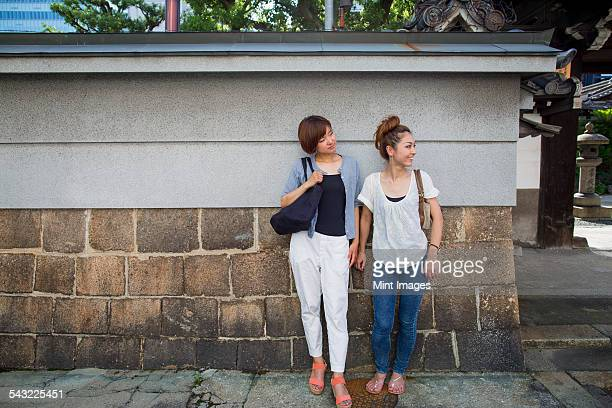Two women standing outdoors, leaning against a wall.