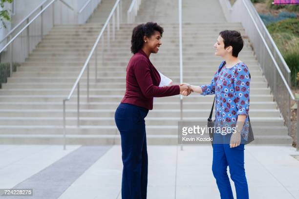 Two women standing outdoors, shaking hands, smiling