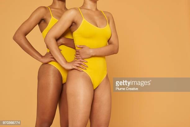 two women standing side by side - farbquadrat stock-fotos und bilder