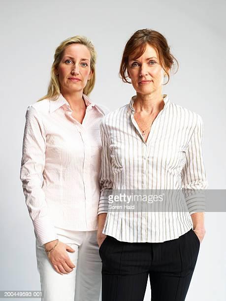 two women standing side by side, portrait - côte à côte photos et images de collection