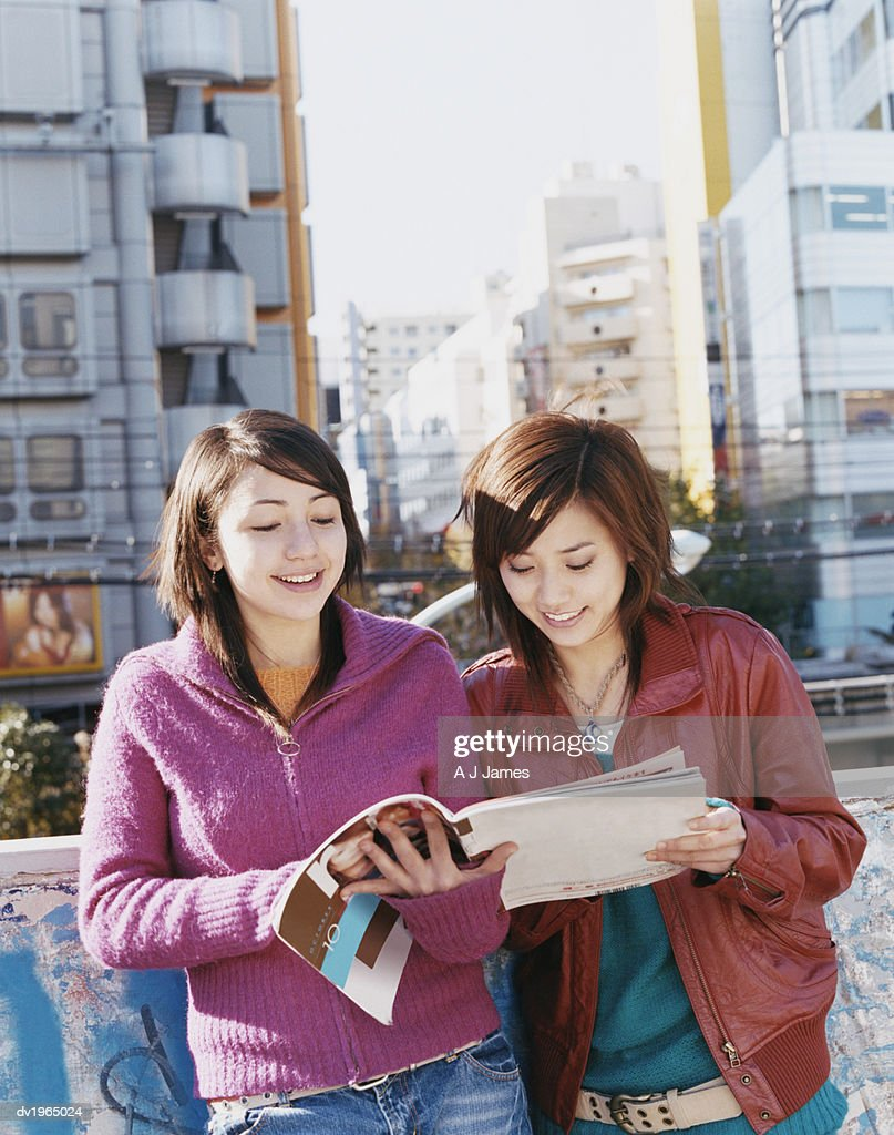 Two Women Standing Side by Side, Reading a Magazine Together : Stock Photo