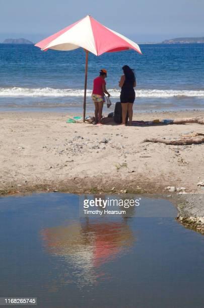 two women standing under red and white umbrella on a beach on tenacatita bay; costalegre, jalisco, mexico - timothy hearsum fotografías e imágenes de stock