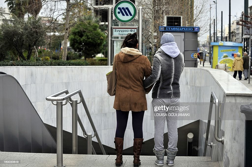 Two women stands in front of a closed metro station entrance in Athens on january 25, 2013 as Greek police have stormed the metro depot in earlier today, breaking up a sit-in by striking workers. The workers had been on the ninth successive day of strike action that has crippled the underground system. Other transport workers have joined the striking metro workers in solidarity , bringing once more Athens public transport to a standstill. AFP PHOTO/ Louisa Gouliamaki