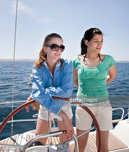 Two women steering yacht