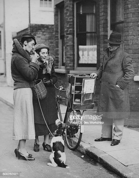 Two women stop to enjoy some hot pies from a street vendor who has a small oven attached to his bicycle while out walking the dog Cliftonville...