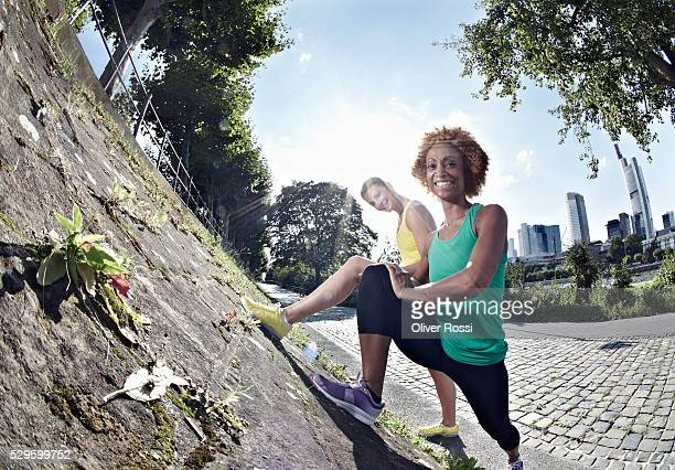 two women stretching in park - wide angle stock pictures, royalty-free photos & images