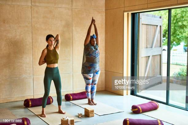 two women stretching in yoga studio - limb body part stock pictures, royalty-free photos & images
