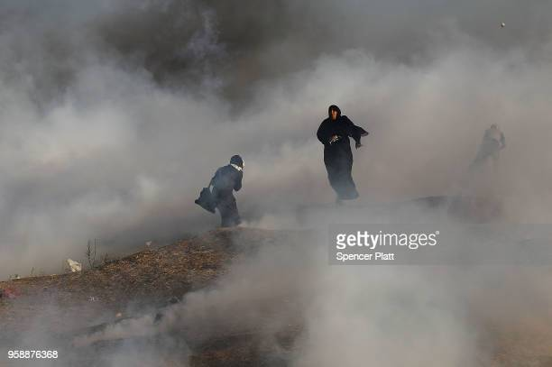 Two women struggle in a cloud of tear gas at the border fence with Israel on May 15 2018 in Gaza City Gaza Israeli soldiers killed over 50...