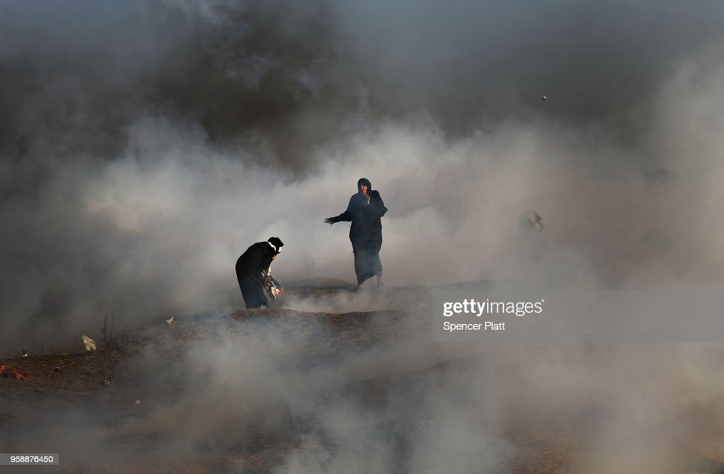 Two women struggle in a cloud of tear gas at the border fence with Israel on May 15, 2018 in Gaza City, Gaza. Israeli soldiers killed over 50 Palestinians and wounded over a thousand as demonstrations on the Gaza-Israel border coincided with the controversial opening of the U.S. Embassy in Jerusalem yesterday. This marks the deadliest day of violence in Gaza since 2014. Gaza's Hamas rulers have vowed that the marches will continue until the decade-old Israeli blockade of the territory is lifted.