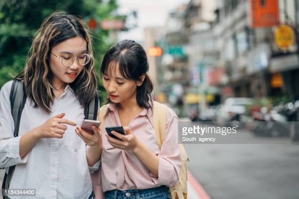 two women students on the street using smart phones - vietnamese ethnicity stock pictures, royalty-free photos & images
