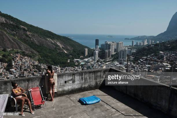 Two women sunbath on a terrace of a multistory construction at the Rocinha favela in Rio de Janeiro Brazil 27 March 2018 Photo Diego Herculano/dpa