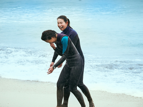 Two women surfers are laughing happily - gettyimageskorea