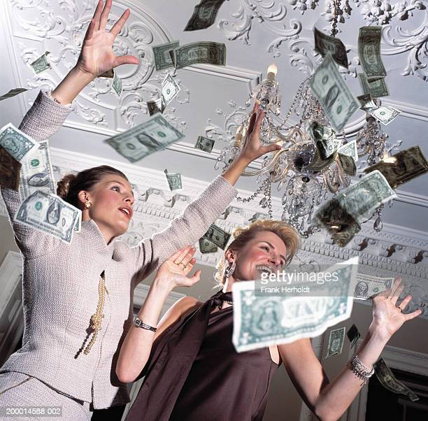 two women surrounded by falling banknotes, low angle view - exceed and excel stock pictures, royalty-free photos & images