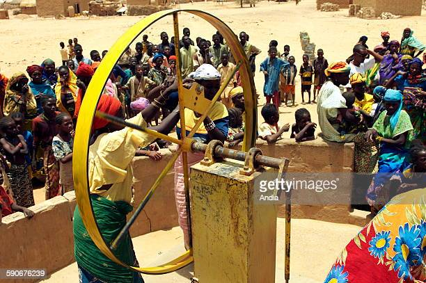 Two women surrounded by the masses operating the yellow gear wheel of a pump to draw some water