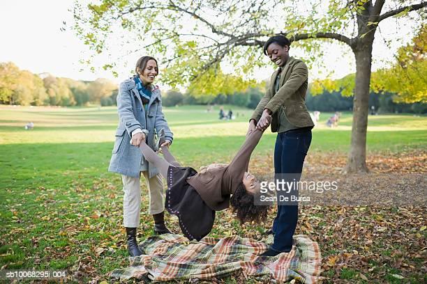two women swinging girl (4-5) in park - プロスペクト公園 ストックフォトと画像