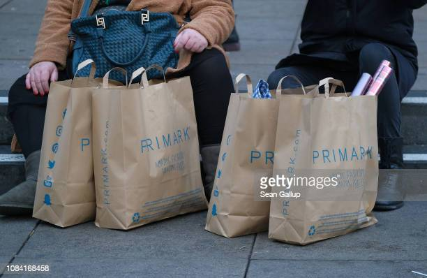 Two women take a rest while carrying shopping bags from discount clothing retailer Primark on December 18 2018 in Berlin Germany With only a week to...