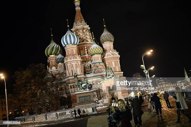 Two women take a selfie photo in front of the Cathedral of Vasily the Blessed commonly known as Saint Basil's Cathedral in Red Square on November 26...