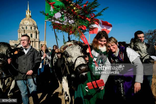 Two women take a selfie with a cow during a public display and reenactment of a tranhumance in front of The Invalides in Paris on February 23 on the...