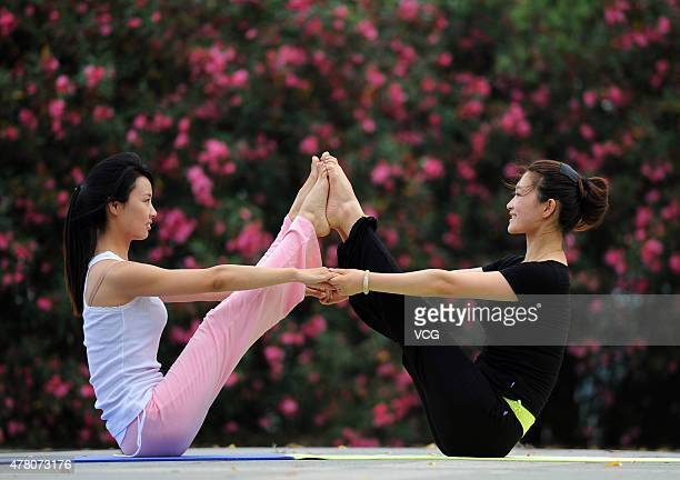Two women take part in a mass yoga session to mark the first International Day of Yoga at a park on June 21 2015 in Huai An China